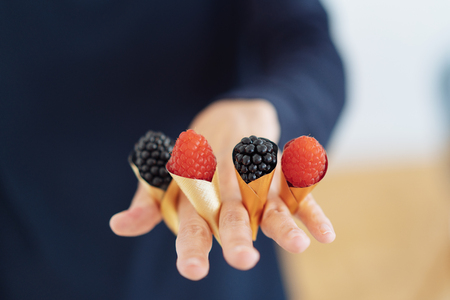 Mixed berries displayed in small cornets held between the fingers on a woman with blackberries and raspberries in a close up conceptual view