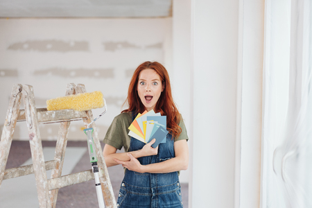 Amazed young woman holding color swatches to her chest in a living room undergoing renovation looking at camera with her mouth open in wonderment