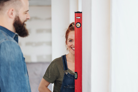 Smiling woman holding a spirit level to one eye watched by her affectionate husband as they do DIY renovations to their home Stockfoto
