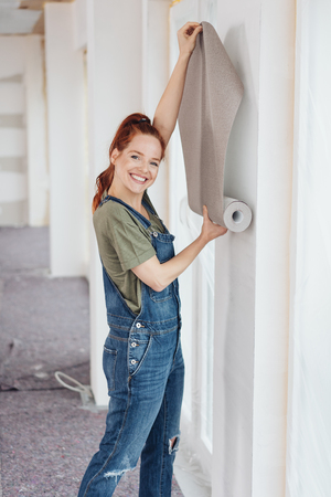 Attractive young redhead woman dong interior decorating in her newly built home holding a roll of wallpaper against a wall with a smile