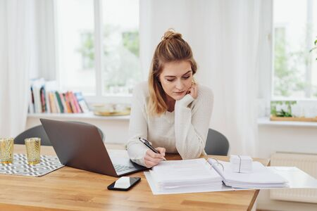 Hardworking young businesswoman or student in an office seated at her desk working on a thick binder of notes with an open laptop beside her
