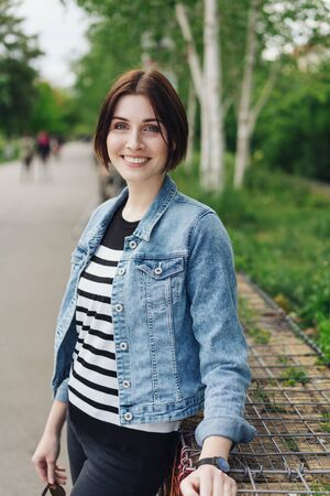 Trendy young woman in a denim jacket standing relaxing leaning against a low wall in an urban park smiling at the camera Imagens