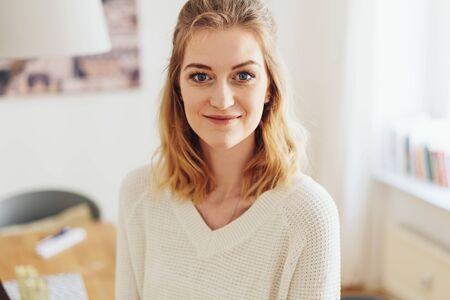 Hübsche junge blonde Frau mit einem freundlichen Lächeln, die zu Hause in einem Nahaufnahmeporträt drinnen steht Standard-Bild
