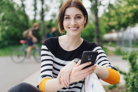 Pretty vivacious young woman relaxing on a bench in a park in town holding her mobile and looking at the camera with a beaming smile