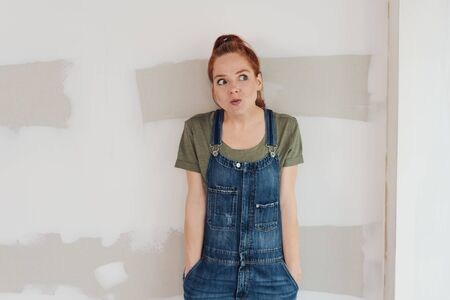 Young woman with a look of gleeful anticipation standing with her hands in the pockets of her denim dungarees in an unfinished room during renovations