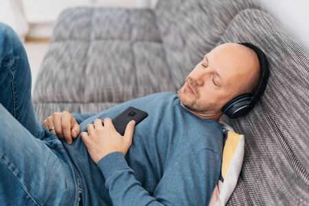 Man relaxing listening to music on stereo headphones on a couch immersed in the soundtrack with closed eyes in a high angle view