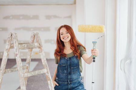 Capable happy young woman holding up a paint roller as she stand alongside a ladder in an unfinished room during renovations