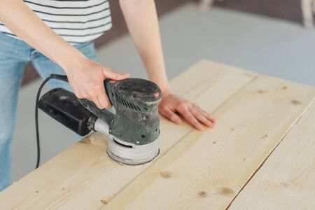 Young woman using a power sander on wooden boards during renovations to her home n a close up view on her hands Banque d'images
