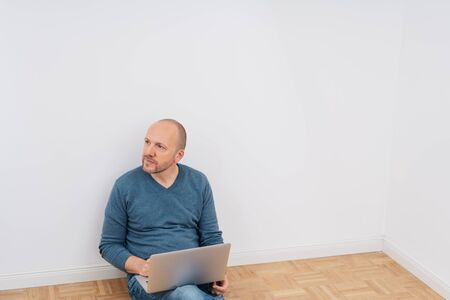 Man in jeans relaxing sitting on a wooden floor leaning against the wall with a laptop on his knees looking off to the side with a pensive expression with copy space above