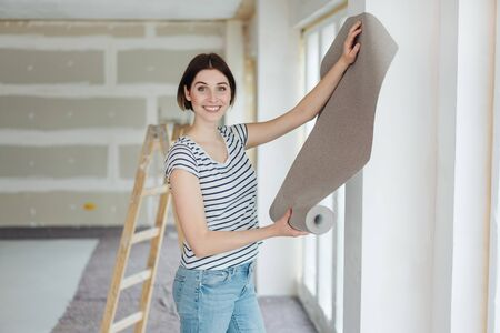 Felice giovane donna appesa carta da parati mentre si fanno lavori di ristrutturazione della casa fai da te in piedi di fronte a una sezione di parete dipinta di recente tenendo un roll up sul display