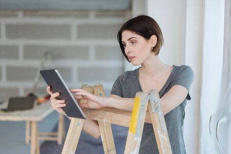 Serious concerned young woman using a tablet as she leans on a stepladder in an unpainted room during renovations