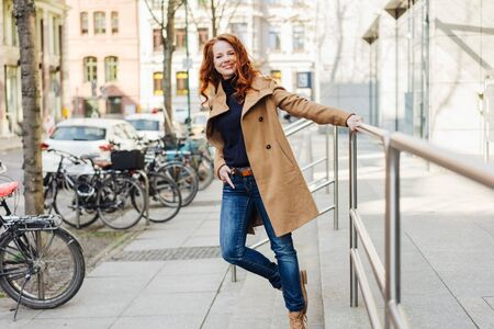 Trendy stylish young urban woman standing holding a railing in a city street with hand in pocket smiling happily at the camera