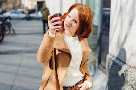 Cute extrovert woman toasting the camera with takeaway coffee and a cheeky smile as she walks down a city sidewalk Stock Photo