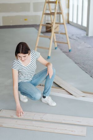 Young woman working with planks of light natural wood on the floor in an unfinished living room during renovations