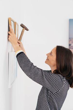 Una mujer mirando hacia los lados mientras usa un martillo para clavar un pequeño marco de imagen en una pared blanca junto a otros dos marcos Foto de archivo