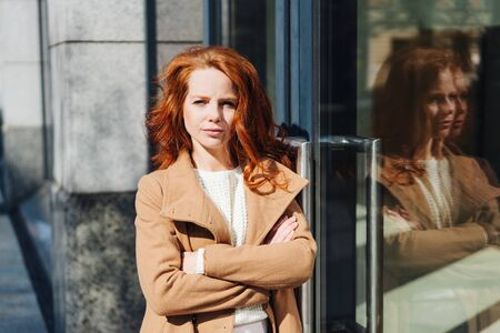 Attractive stylish young redhead woman scrutinising the camera with folded arms and a pensive expression outside a commercial building with reflection in the window Фото со стока