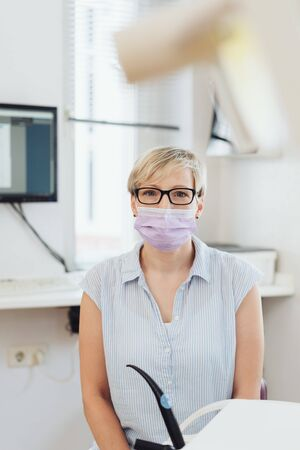 Female dental nurse or dentist in the dental surgery seated next to the equipment and suction pump