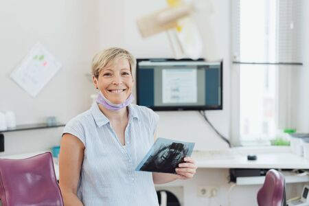 Happy friendly female dentist holding an X-ray as she stands alongside the dental chair in her surgery 免版税图像
