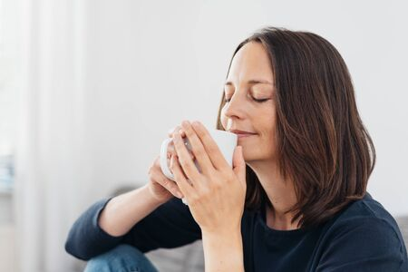 Woman savoring the aroma of a mug of hot coffee with a blissful smile and closed eyes