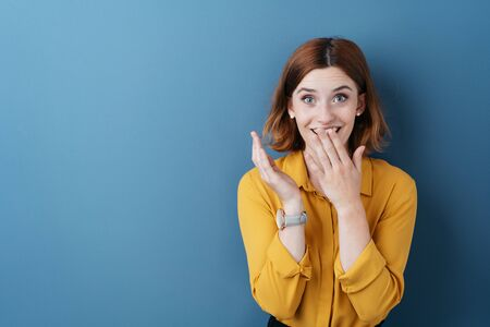 Surprised young woman covering her mouth with her hand as she stares at the camera in wide eyed astonishment over blue with copy space
