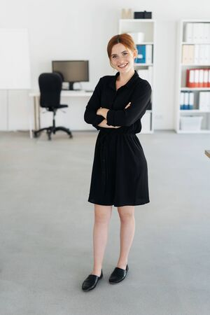 Pretty young businesswoman in a spacious light office standing with folded arms looking at the camera with a warm friendly smile in a full length portrait 版權商用圖片