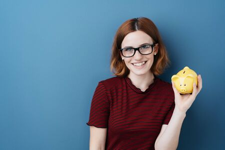 Happy young woman wearing glasses holding up a piggy bank in her hand as she anticipates the things she can do with her savings, over blue with copy space