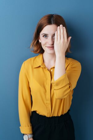 Attractive young woman covering one eye with her hand as she grins at the camera over a blue background