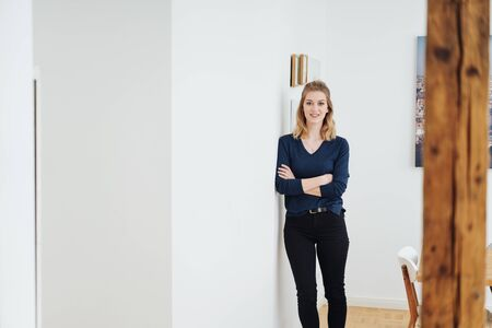 Smiling slender casual young woman with folded arms standing in a passageway at home leaning against the wall looking at the camera, with copy space