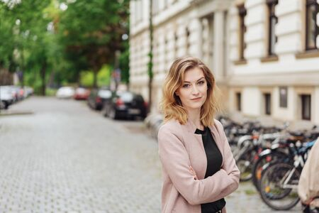 Attractive young blond woman in a quiet paved street in town standing with folded arms looking pensively at the camera in front of a historic building Banco de Imagens