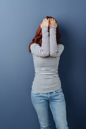 Young redhead woman in denim jeans and striped top standing in front of a blue background hiding her face behind her arms with hands raised to her forehead