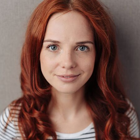 Pretty young redhead woman with a quiet smile looking into the camera with big eyes in a close up cropped head shot