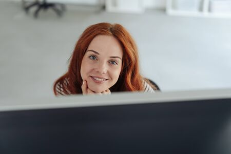 Happy friendly young businesswoman in an office sitting with her chin on her hand looking attentively at camera over her computer monitor