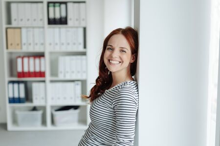 Happy relaxed young woman with a beaming smile standing leaning against an interior wall in the office Фото со стока