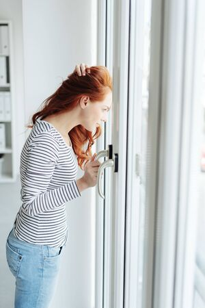 Young woman standing watching through a glass door staring outside intently with a hand to her long red hair as she waits indoors Foto de archivo