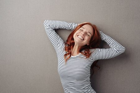 Funny young woman giving a big cheesy grin as she poses with her hands on her head over a grey background Фото со стока