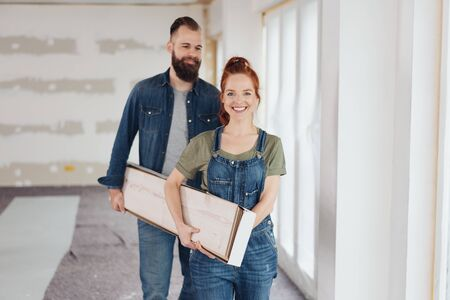 Happy young couple doing home improvements walking through a newly renovated room carrying a box of wooden planks Stock Photo