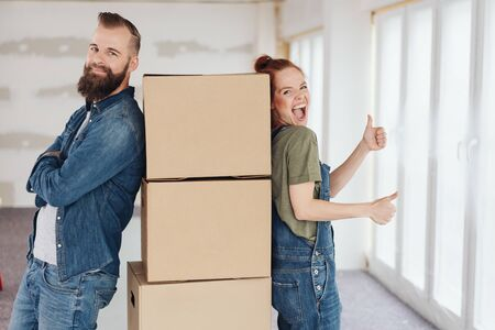 laughing vivacious woman giving a double thumbs up as she and her husband stand leaning against stacked cardboard boxes in their new home Фото со стока