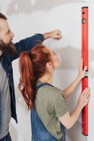 Young couple checking a new build wall with a builders spirit level during renovations to their house