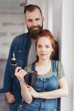 Pareja joven capaz haciendo renovaciones de bricolaje en su nuevo hogar posando junto con la mujer sosteniendo un taladro eléctrico en su mano