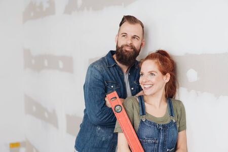 Young couple admiring their DIY renovation work on their home standing holding a spirit level and smiling happily in satisfaction