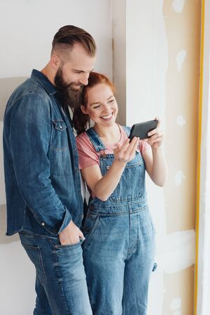 Happy young couple in denims looking at a mobile phone with happy smiles in an incomplete new build room at home 免版税图像