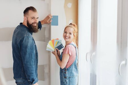 Smiling happy couple choosing paint colors for their newly renovated living room holding up assorted swatches to the wall