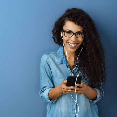 Happy young woman with a warm friendly smile standing listening to music on her mobile phone against a blue studio background Imagens