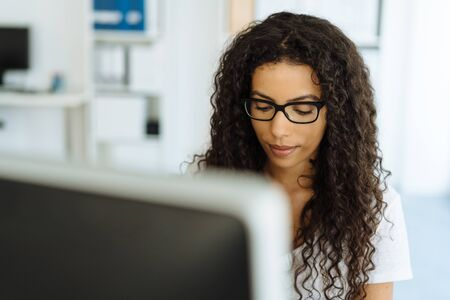 Serious young businesswoman concentrating on her work as she sits at a desktop computer in the office viewed over the monitor