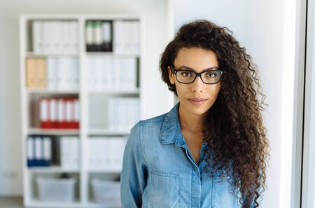 Serious attentive young businesswoman wearing glasses standing in an office staring at camera with a thoughtful expression
