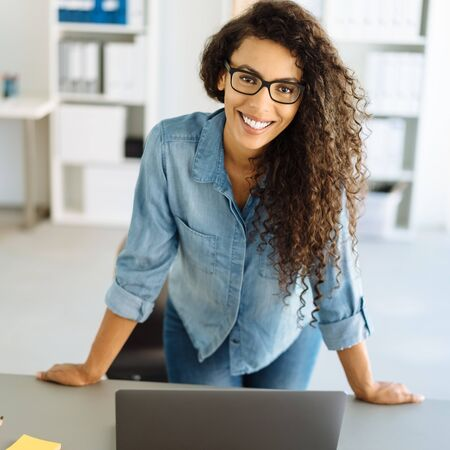 Happy friendly young businesswoman standing leaning on a desk in the office looking at the camera with a warm welcoming smile