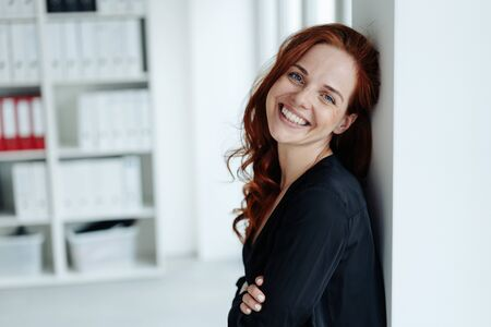 Happy confident friendly young businesswoman leaning against an office wall grinning at the camera with a friendly smile
