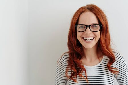 Portrait of a beautiful cheerful young woman with long curly red hear laughing happy while wearing eyeglasses with black frames and a striped long sleeve T-shirt
