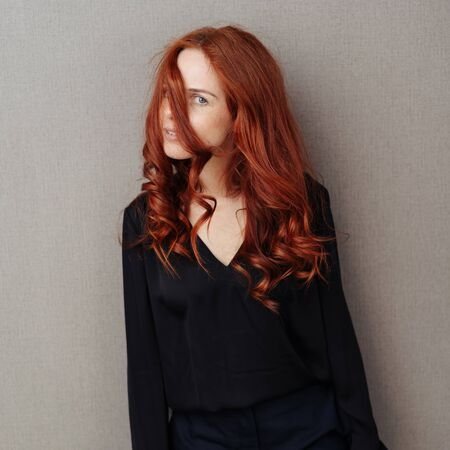 Beautiful young woman with curly long red hair looking sideways at the camera with a strand of hair across her face over a grey background Stockfoto
