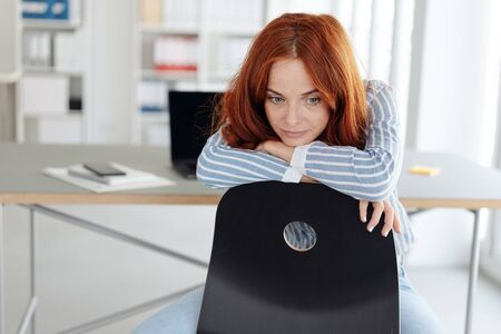 Glum young woman staring at the floor while leaning over the back of her chair at the office